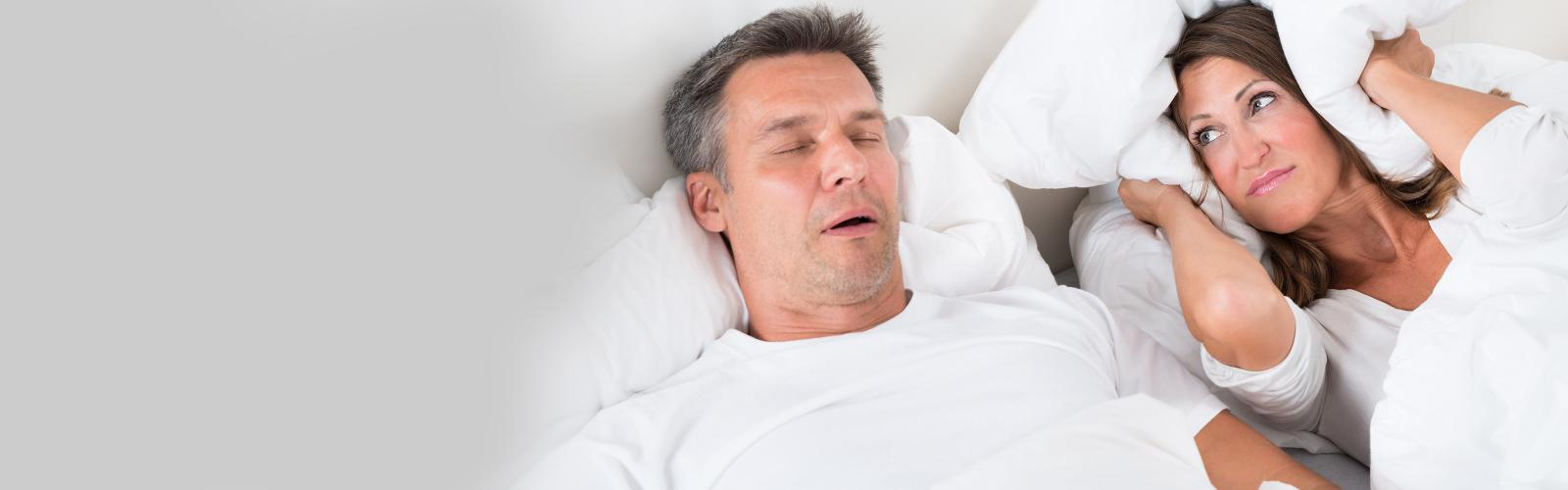 Snoring man with annoyed partner in bed
